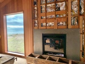 Gas fireplace and surround, new window with views to rainy coastline