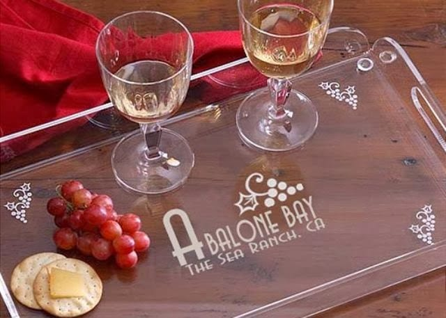 Clear tray etched with Abalone Bay, The Sea Ranch, CA holds 2 wine glasses with white wine, red grapes and 2 crackers one with cheese. Red napkin near by