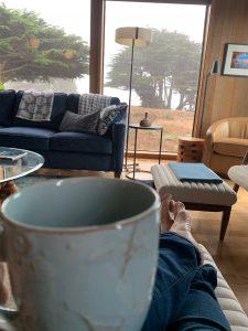 holding cup of tea, bare feet on ottoman watching rain on window in The Sea Ranch