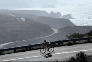 Solo biker riding highway 1 south towards Jenner by the Bay , Sonoma County, Ocean in the background