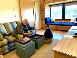 Father and son play dice on ottoman's tray in game room, chess game is set up next to them