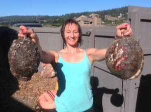 Woman showing abalone in each of her hands