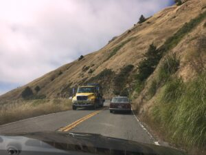 truck and car pass on narrow coastal cliff road, highway 1