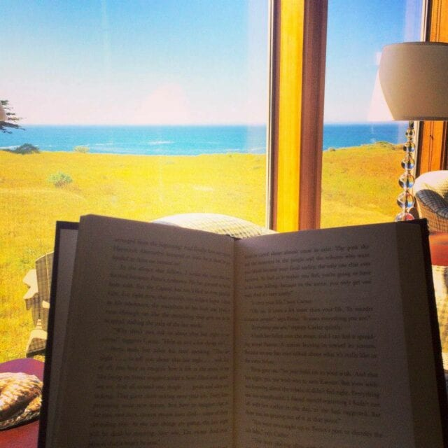 open book in front of picture window of Sea Ranch Abalone Bay vacation rental viewing grassy ocean bluff and ocean in the distance