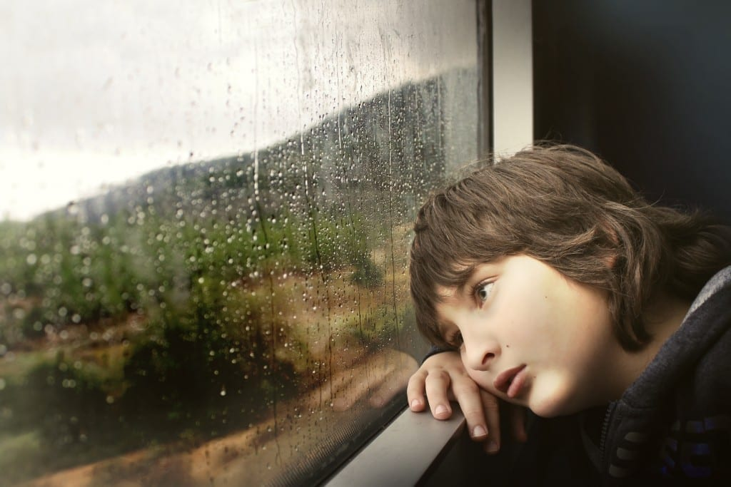 boy sadly looking out window at rain