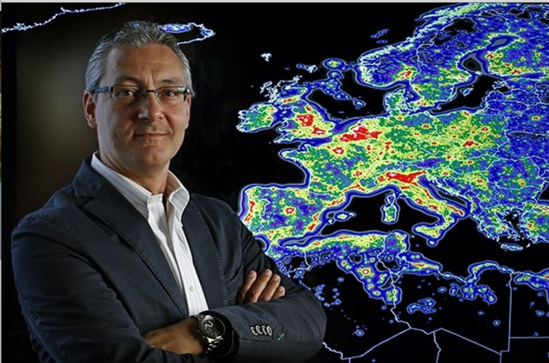 Fabio Falchi, stands arms crossed in front of the map of Europe's light pollution in Europe.