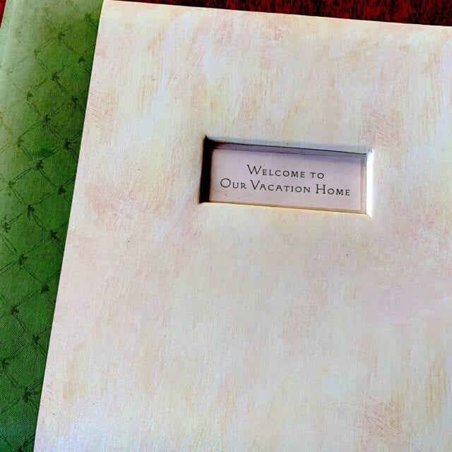 "closed guest book, green binding with parchment designed cover, titled, ""Welcome to Our Vacation Home"""