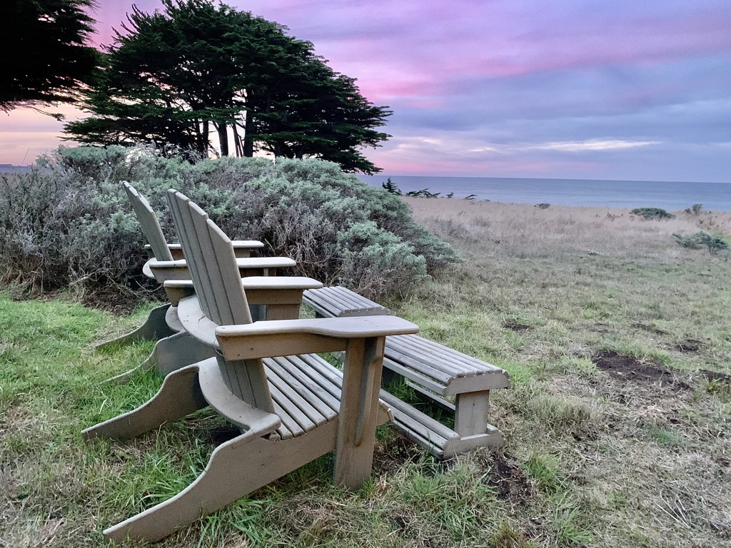 Adirondack chairs look to purple sunrise
