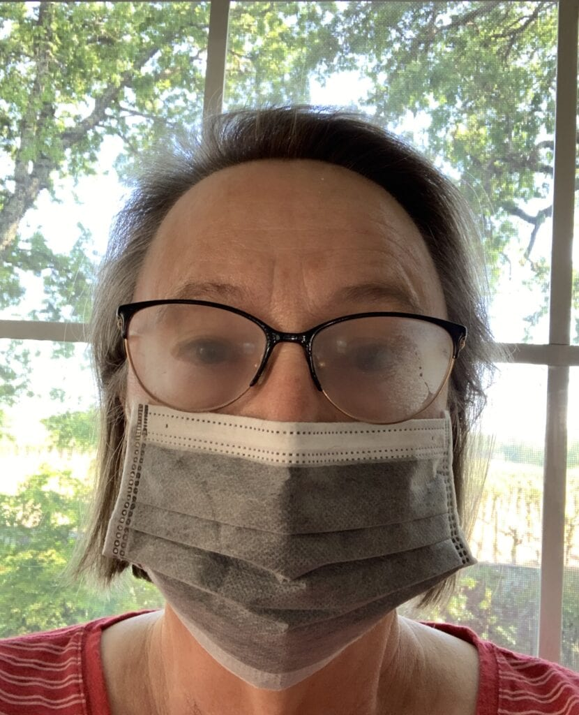 woman wearing face mask with glasses background of trees and vineyard