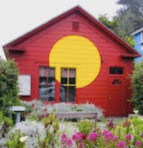 Red house with bring yellow circle in the middle of side of the houseCoast Highway Artists Collective