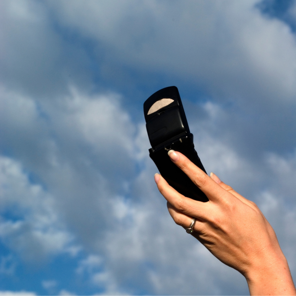 phone in woman's hand held up to sky with clouds
