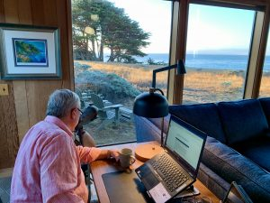 man looking through binoculars to ocean while working with computer on desk