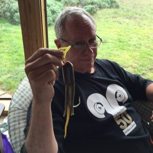 Jorge shows his ling cod jig he made sitting in chair wearing black t-shirt with 50th anniversary Sea Ranch Logo