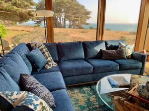 Blue sectional sofa in front of windows showing ocean views